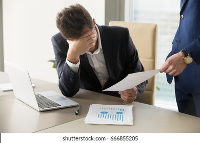 Sad manager getting notice of dismissal, sitting at workplace with laptop and financial documents, employee receiving letter with bad news, entrepreneur upset by commercial failure or firm bankruptcy
