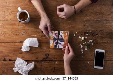 Sad mans, womans hands holding torn picture of romantic couple.