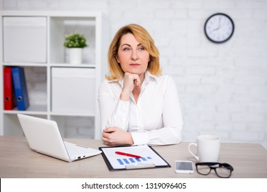 sad mature business woman sitting in modern office
