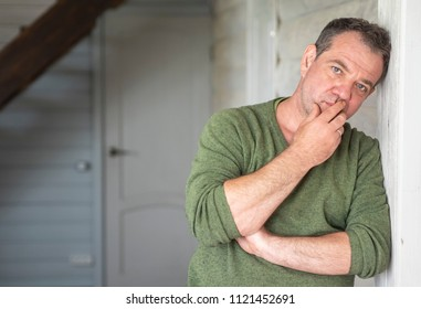Sad mature Caucasian man in green jumper stands leaning his back on a wooden wall inside the house