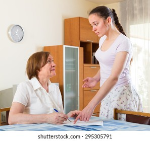 Sad mature couple of  women with  documents at table in home