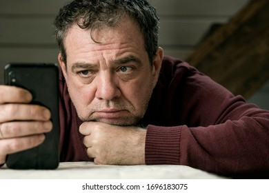 Sad mature man with smartphone at the table at home in a dark room