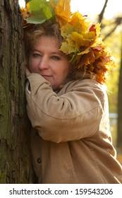 sad mature woman near tree looks at camera