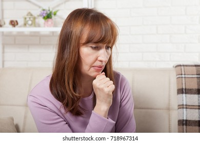 Sad middle age woman sitting on a sofa in the living room. Menopause