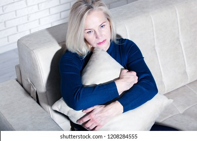 Sad middle aged woman sitting on a sofa in the living room