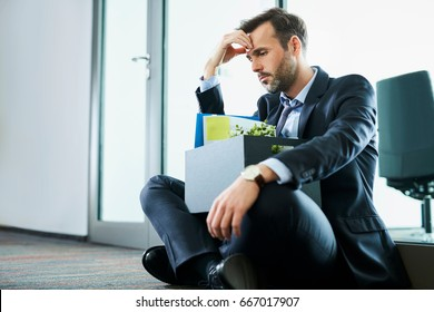 Sad middle-aged businessman sitting with his personal belongings after losing his job