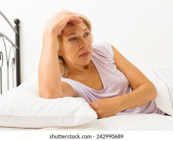Sad middle-aged female with head reclined upon hands in bed
