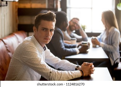 Sad millennial man not looking at multiracial friends smiling and having fun drinking coffee in cafe, frustrated male feeling jealous of diverse happy people sitting near. Loner, outcast concept
