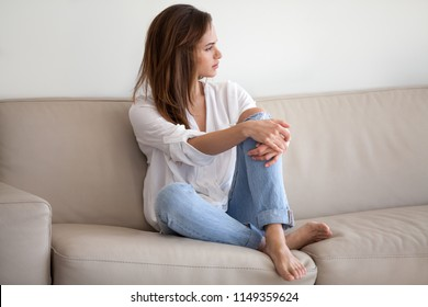 Sad millennial woman sit on couch looking far away, thinking about problems with boyfriend