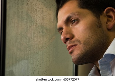 Sad mirrored young man is depresed, gray background