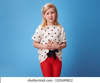 sad modern child in red pants with abdominal pain against blue background