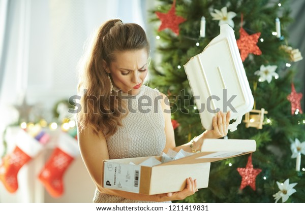 sad modern woman near Christmas tree pulling out a broken dish from the parcel
