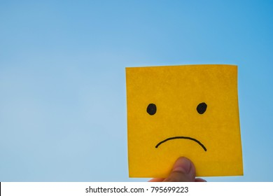 Sad mood on yellow sticky note with blue sky background. The concept of negative mood and negative thinking.