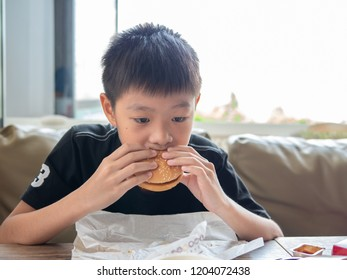A sad moody boy eating hamburger in the hamburger shop
