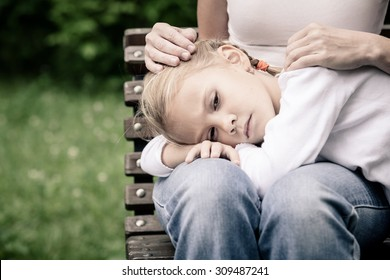 Sad mother and daughter sitting on bench in the park at the day time.