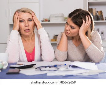 Sad mother and her adult daughter with big financial problems are sitting at home