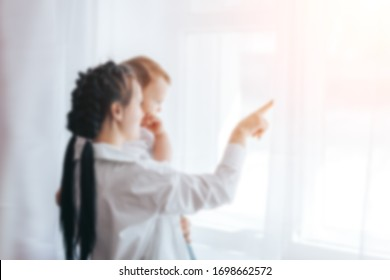 Sad mother sitting next to the window with baby on her shoulder, She is waiting for a doctor or husband. She is tired and frustrated. Unfocused photo, blurred background.