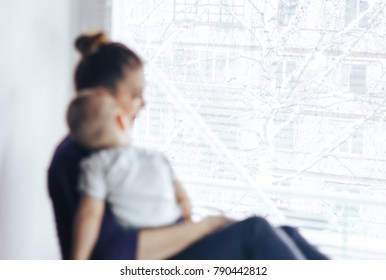 A sad mother sitting next to the window with a sleeping baby on her shoulder, She is waiting for a doctor or husband. She is tired and frustrated. Bad news. Family unfocused, focus on window.