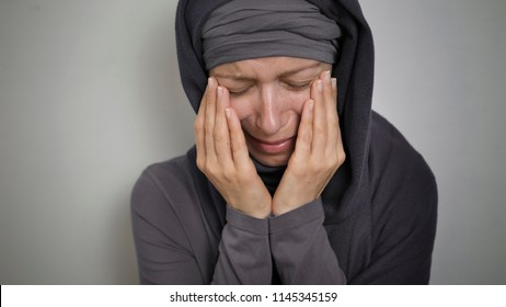 A sad Muslim woman in a hijab, crying. Close-up of a weeping Arab girl.