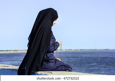Sad Muslim woman sits on the Bank of the river, with a rosary in his hands.