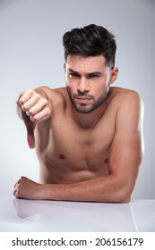sad naked man making the thumbs down hand sign in studio