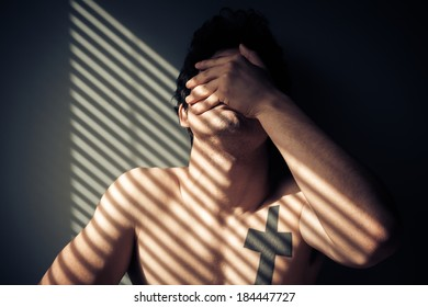 Sad naked man sitting by the window with shadows from blinds on his face