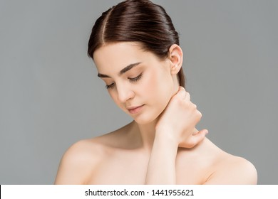 sad naked woman touching neck isolated on grey