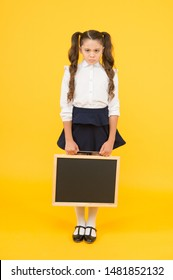 Sad news. Schoolgirl offended pupil informing you. School girl hold blank chalkboard copy space. Announcement and promotion. Girl school uniform hold blackboard. Back to school. Something happened.