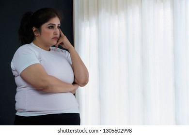 Sad obese woman looks while standing by the window