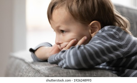 Sad offended child feeling bad, lonely and depressed, thinking over conflict with parents. Upset preschooler boy on couch going through age problems and crisis, frustrated about punishment. Close up