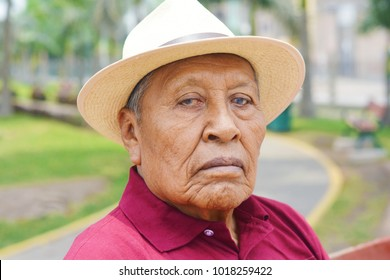Sad old latin man wearing hat in the summer park.