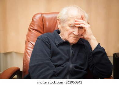 sad old man with a hand on his forehead