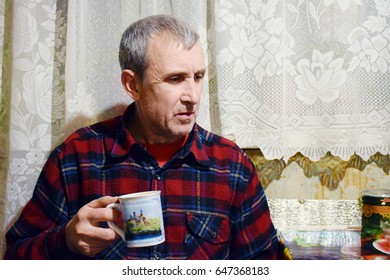 Sad old man holding a cup