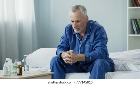 Sad old man sitting in bed and looking at pills, medication and healthcare