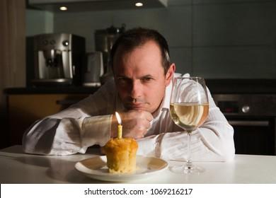 Sad old man sitting at table, celebrating a birthday alone and sad looking at a cupcake