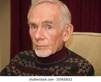 Sad old man staring straight ahead