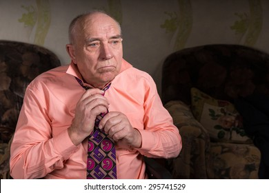 Sad old man tying his tie
