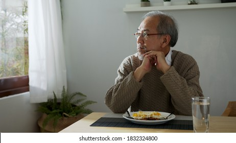 Sad old retired gray haired grandpa asian man sitting alone at table desk at window boring stay home self isolation quarantine feeling depress in problem mental health.