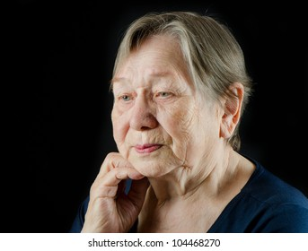 Sad old senior woman looking down and crying