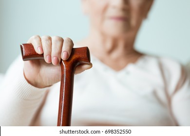 Sad older lady's hand placed on wooden walking stick