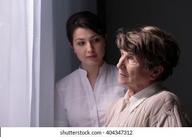 Sad older woman in nursing home waiting for relatives
