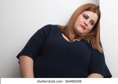 sad overweight woman leaned against a wall