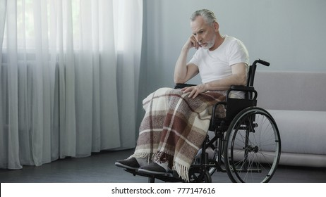Sad pensioner sitting in wheelchair and waiting for his family at nursing home