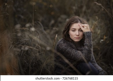 sad and pensive beautiful brunette woman in casual clothes (sweater and jeans) sits among the tall grass, the concept of depression and loneliness,