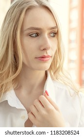 sad pensive beautiful young transgender with long blond hair in white blouse looking aside
