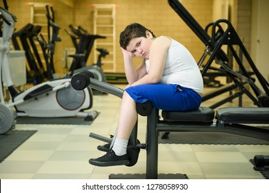 sad pensive fat little boy sitting on fitness equipment indoors gym solving overweight problem