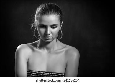 sad pensive girl portrait on black background, monochrome image