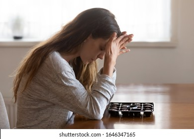 Sad pensive girl sit at table with box of chocolates feel depressed eat candy in stressful situation, thoughtful desperate young woman look at sweets suffer from eating disorder, dieting concept