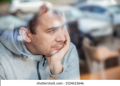 Sad pensive handsome man leaning head on hand in cafe, looking through a window with reflections.