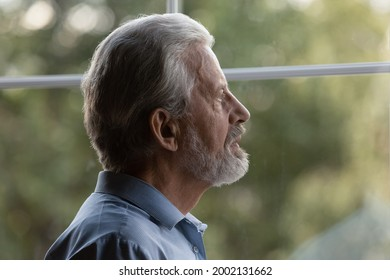 Sad pensive older senior 70s man lost in thoughts looking out window, suffering from memory loss, dementia, Alzheimer disease, feeling loneliness. Old age problems, elderly healthcare concept